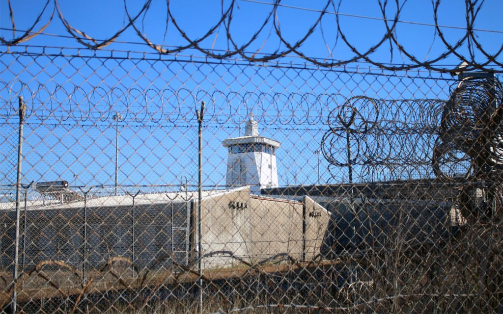 A grey concrete building with guard tower, seen through razor wire fencing.
