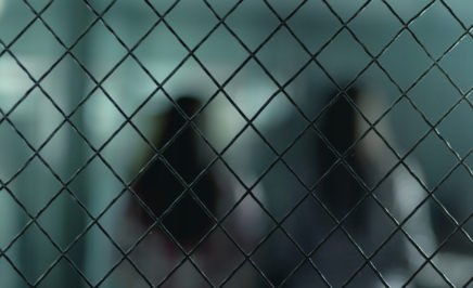 Blurred outline of two women with backs turned, behind fencing