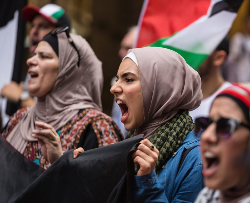 Women in Muslim and traditional Palestinian costume holding a banner and chanting slogans.