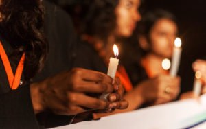 people marching behind a banner, holding candles. Shot is a close up of a hand holding candle.