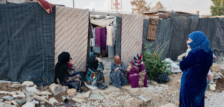 Four woman sitting in a refugee camp