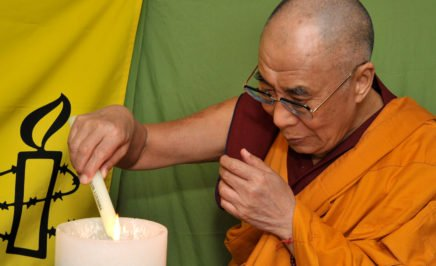 The Dalai Lama lights a candle, one of 30 corresponding to 30 Articles of the Universal Declaration of Human Rights, on World Refugee Day.