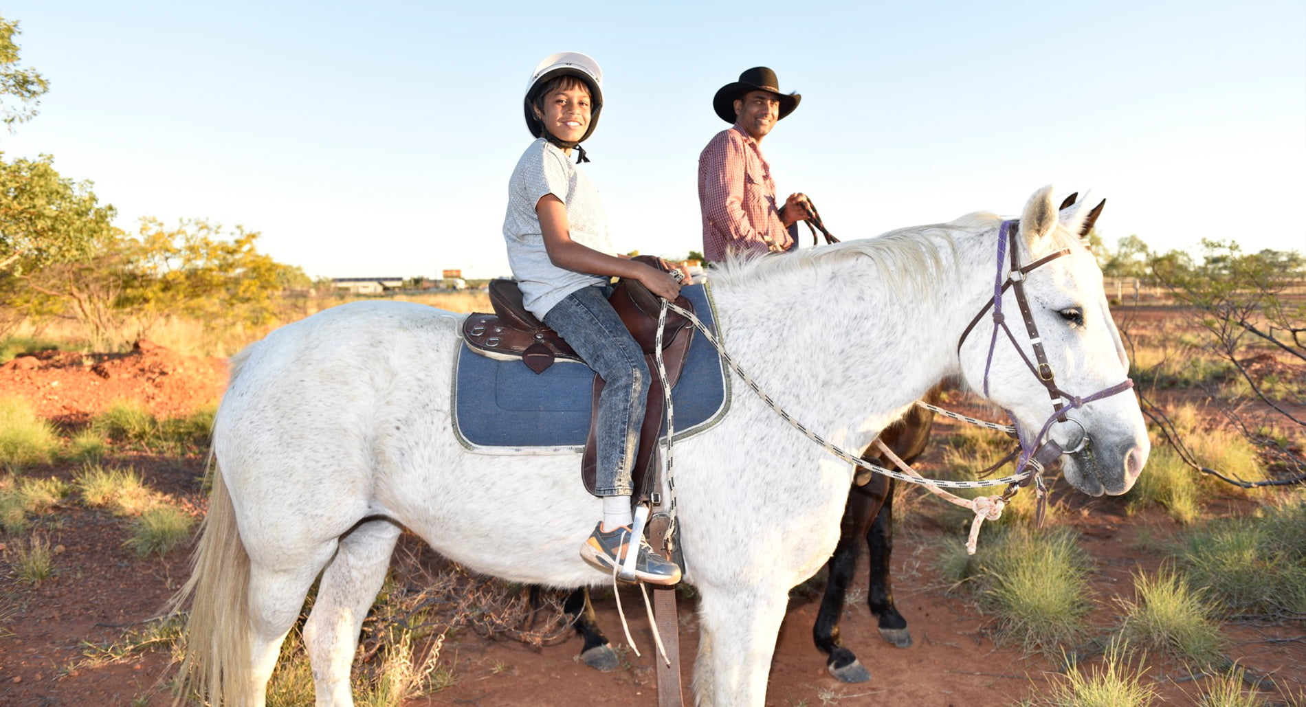 A boy rides a horse with co-founder David Sammon as part of Mona's Cultural Horsemanship program on Flora Downs Station, near Mount Isa, June 2016. © Wayne Quilliam