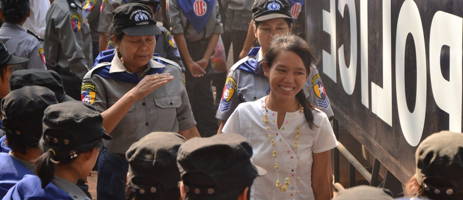 Student activist Phyoe Phyoe Aung smiling while she is escorted by policewomen