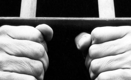 Black and white photograph showing hands of an anonymous prisoner gripping the bars of a prison cell.