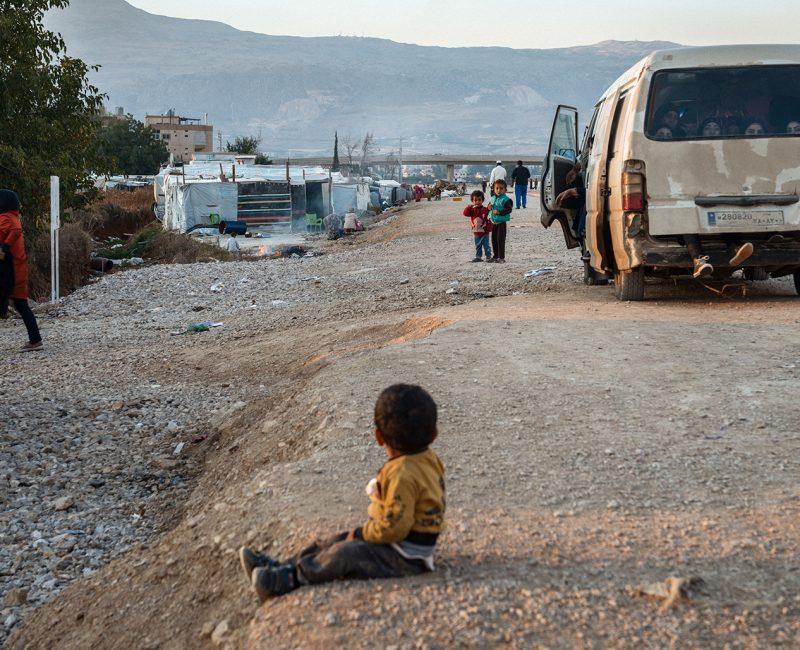Syrian boy sits on a roadside in Lebanon