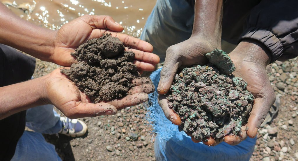 A close up photograph of Artisanal miners hold up handfuls of cobalt ore (left) and copper ore (right) in the Democratic Republic of the Congo in May 2015.