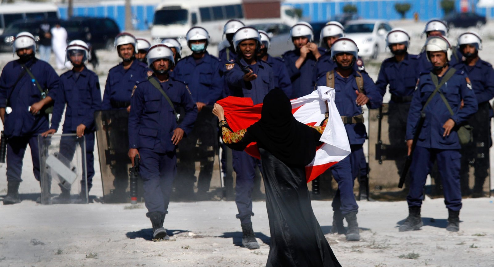 An anti-government protester holds a flag in front of a line of police in Bahrain.
