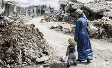 A Kurdish Syrian woman walks with her child past the ruins of the town of Kobane