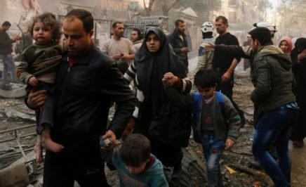 Syrians make their way through debris following air strikes in Aleppo, Syria on January 13, 2016.