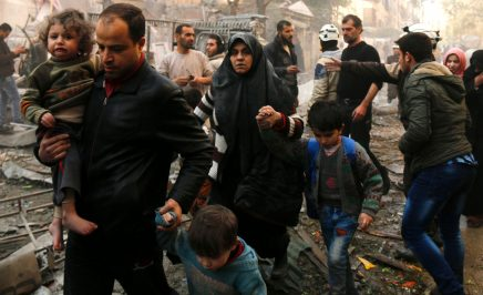 Syrians make their way through debris after air strikes in the rebel-controlled side of Aleppo on January 13, 2016.