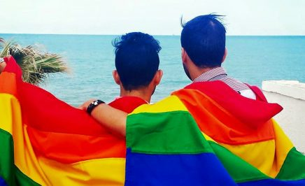 Two people wearing rainbow flags in Tunisia