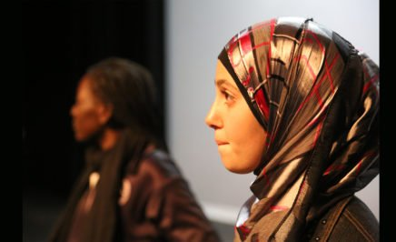 a young woman wearing a hijab on stage