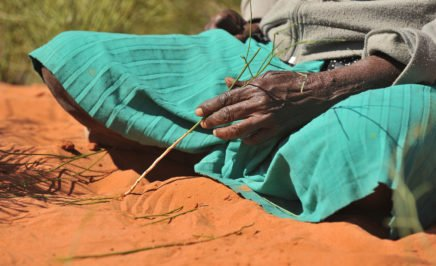 Aboriginal woman making a sand painting in NT, Australia.