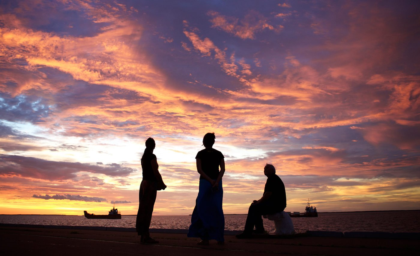 Three Indigenous people silhouetted at sunset by the ocean