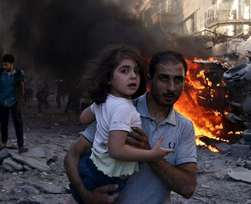 A man carries a young girl through rubble in Syria.