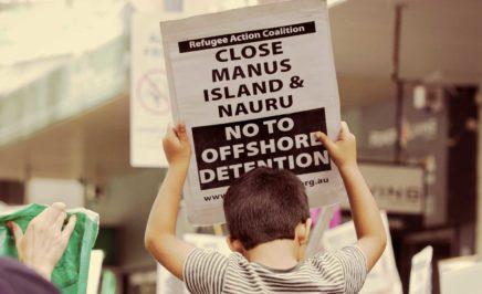 Boy holds a close Manus and Nauru sign