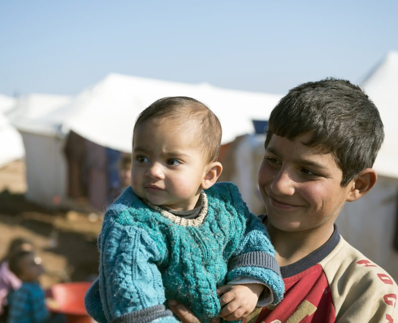 A smiling boy holds a baby, with white tents behind him