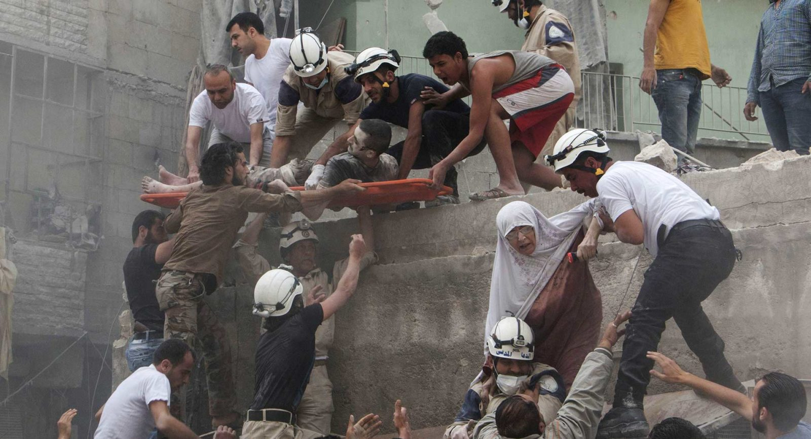 Syrian rescue workers and citizens evacuate people from a building following a reported barrel bomb attack by Syrian government forces.