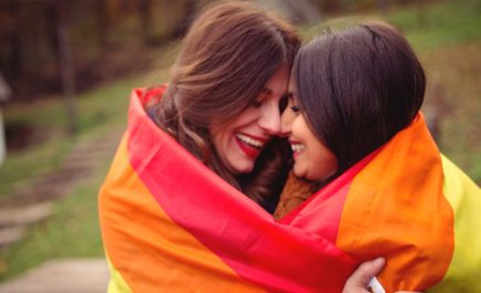 Two women embracing inside a rainbow flag