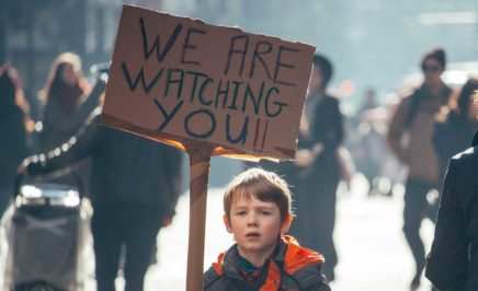 Young boy holding sign which says 'we are watching you'