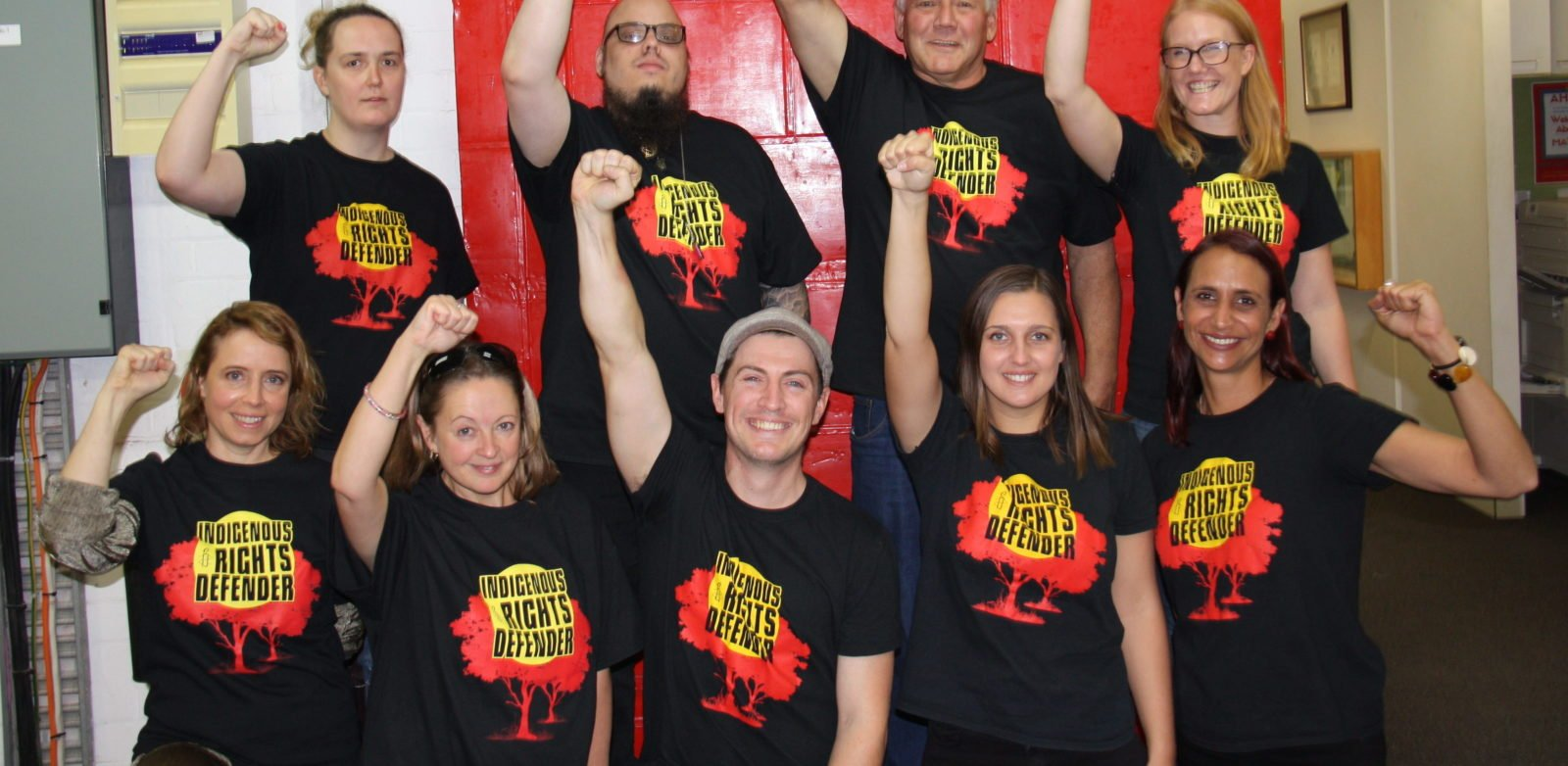 9 people with their fists held high with Indigenous Rights Defender on their t-shirts