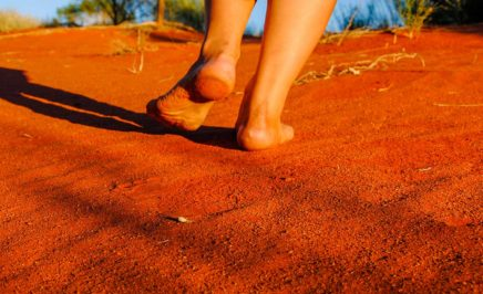 Walking barefoot on red sand dune