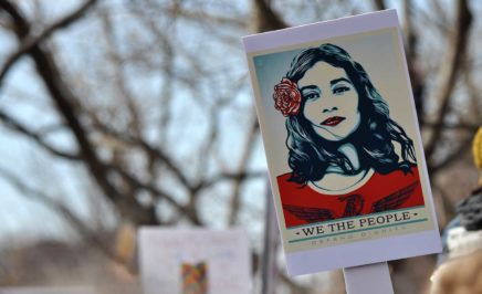 A protester holds up a poster of a woman with a rose behind her ear, as designed by artist Shepard Fairey.