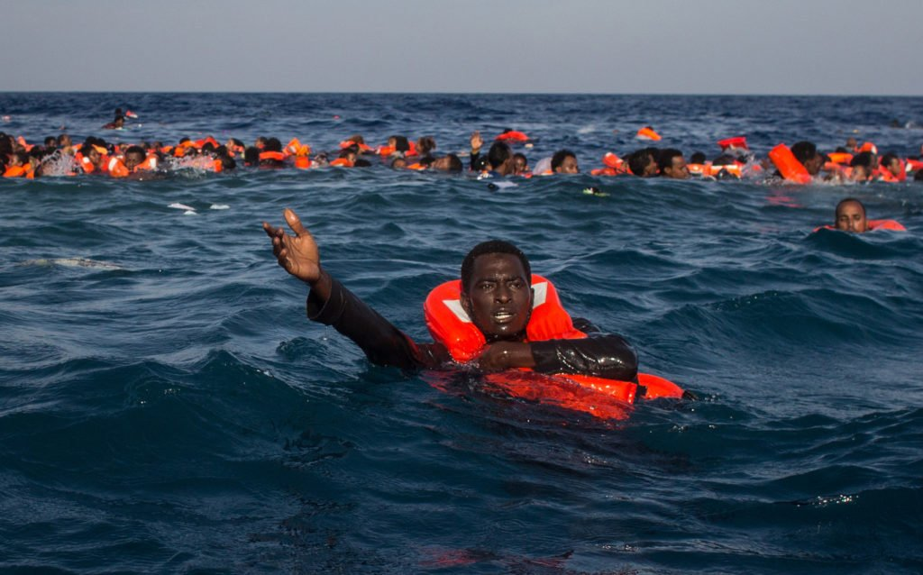 MAY 24: Refugees and migrants are seen swimming and yelling for assistance from crew members. © Chris McGrath/Getty Images