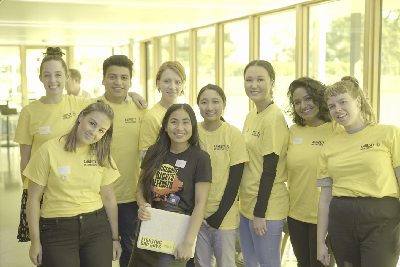 A group of volunteers wearing Amnesty yellow volunteer Tshirts & on in a black Indigenous Rights Tshirt are posed for the photo