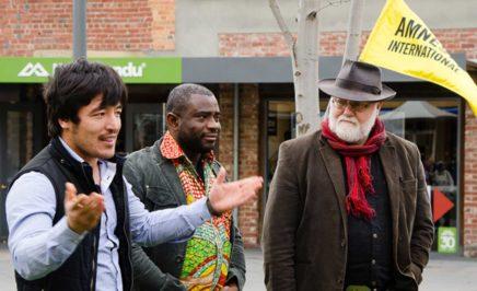 Alderman Bill Harvey from Hobart City Council, John Kamara from the Sierra Leone community and Haji Alizada a local Hazara man, opening the tree for the Tasmania Refugee Group's event