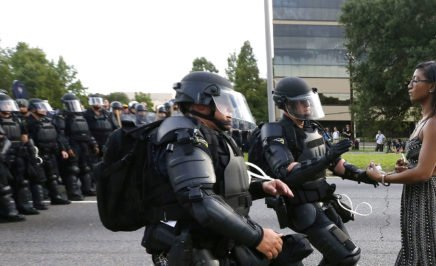 A black female demonstrator stands still in the street as US police officers in riot gear rush toward her. Behind them is a line of police officers also in riot gear.