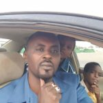 Mahadine, an online activist imprisoned in Chad, sits in his car with his sons.