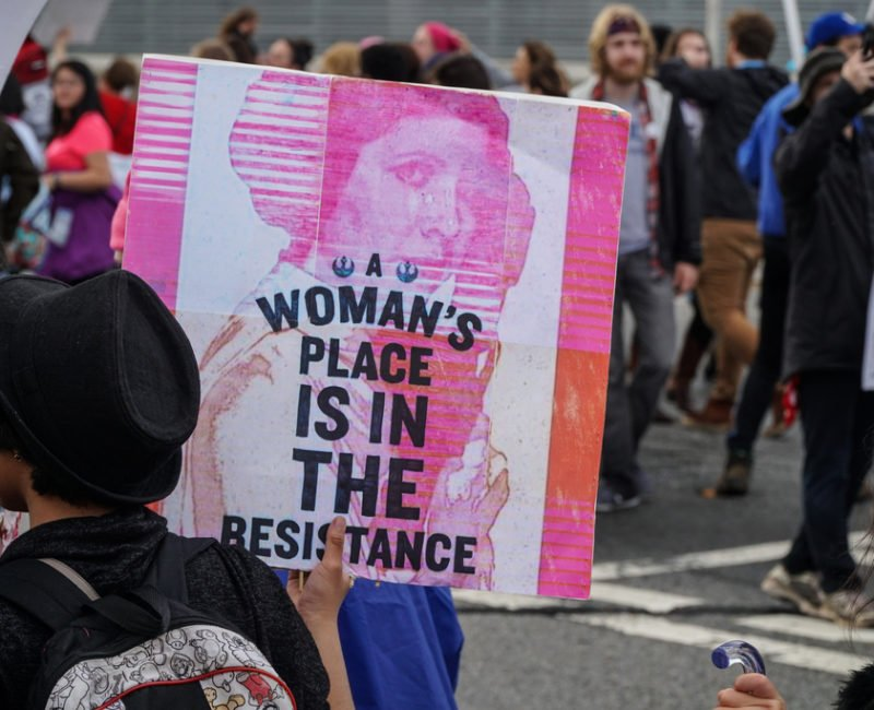 A photograph of a protester in a crowd of people at the women's march on Washington in January 2017. She is holding a sign featuring Carrie Fisher as Princess Leia from Star Wars with the caption 'A women's place is in the resistance'.