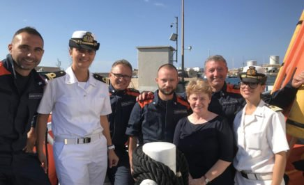 Claire Mallinson with members of the Italian Coast Guard who work to protect people at sea. © AI