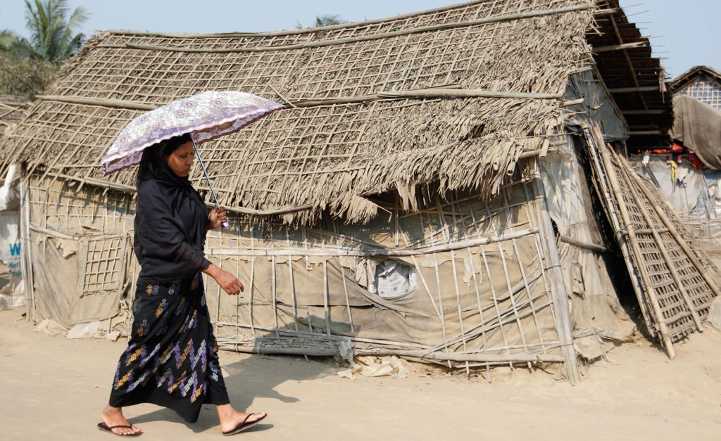 A Rohingya woman shields herself from the sun in the displacement camps outside Sittwe township, Rakhine State, Myanmar