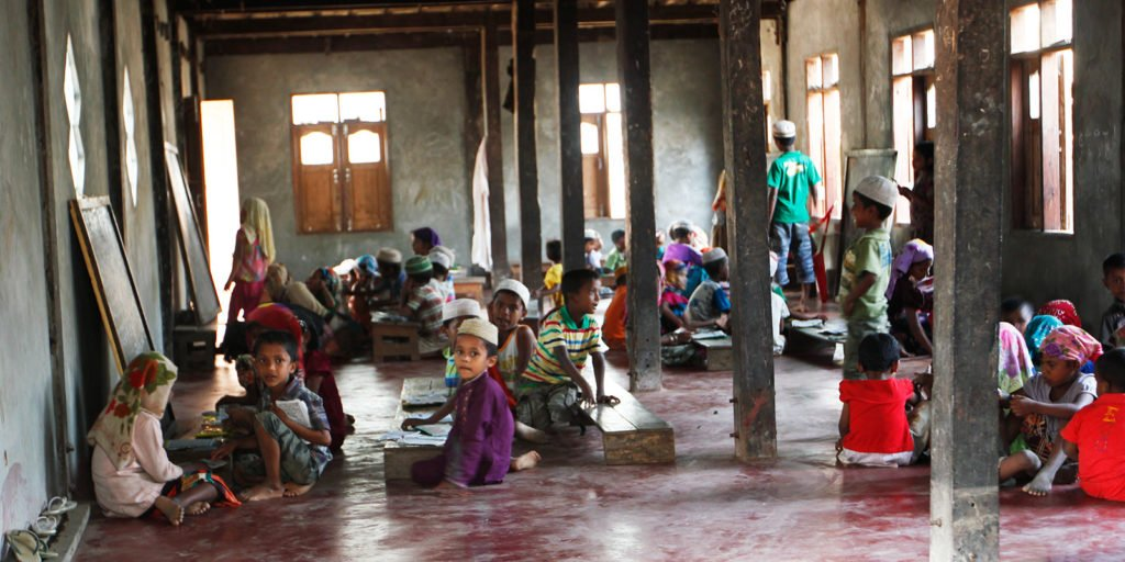 Rohingya children sitting on a red concrete floor in a sparsely furnished room. Some are looking toward the camera and others are engaged in school lessons.