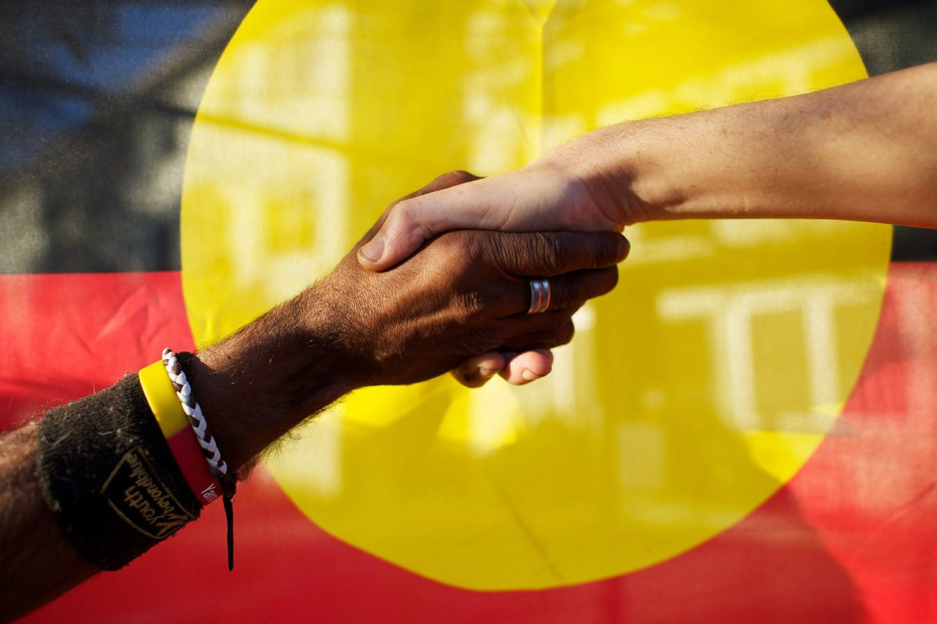 Indigenous and Non-Indigenous Australians shaking hands in front of the Aboriginal flag