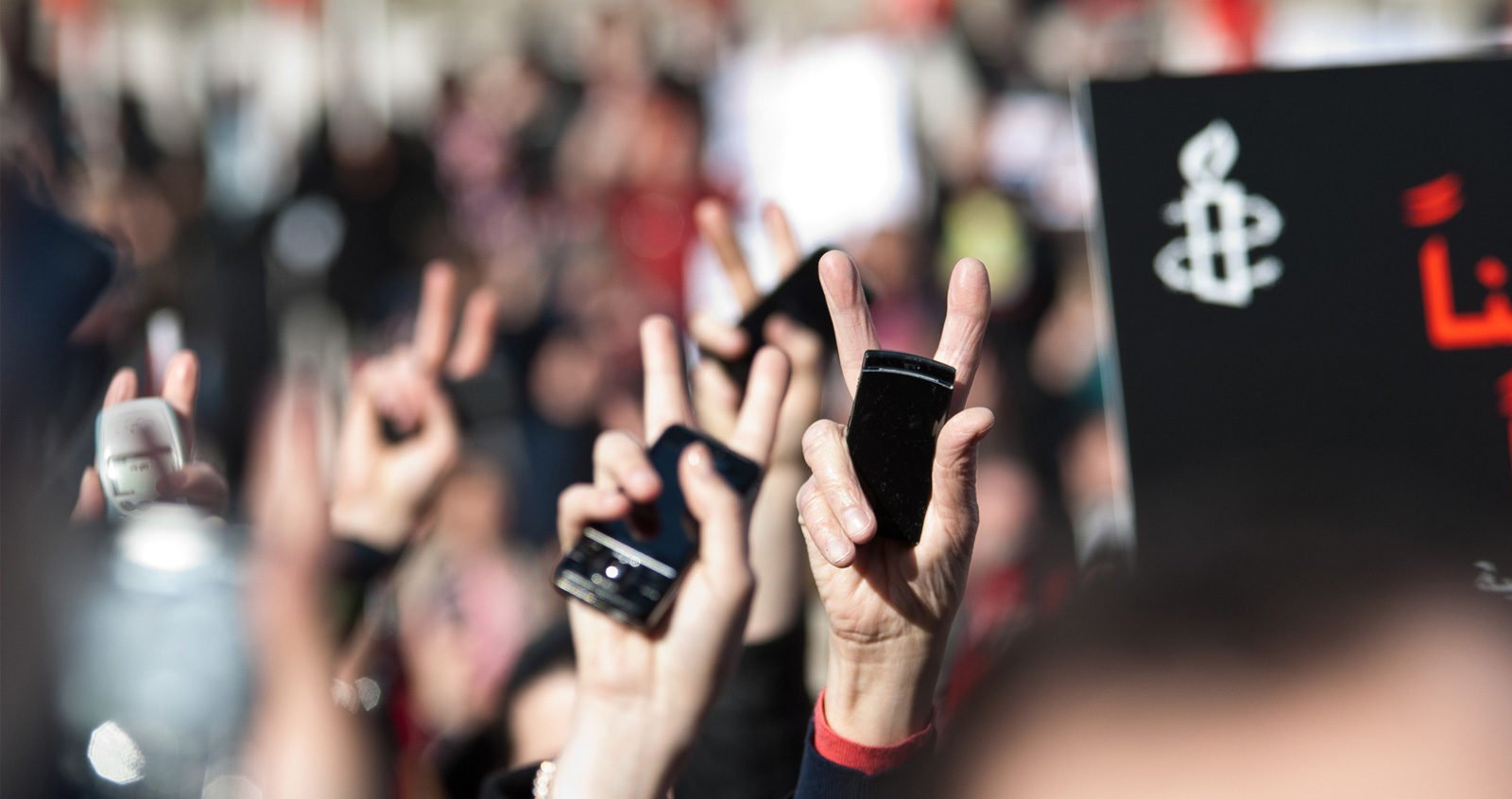Protestors hands holding mobile phones
