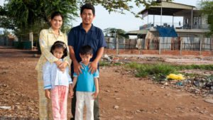 Cambodian rights activist Tep Vanny standing with her husband and two child, a boy and a girl, smiling at the camera. The family are outside, standing on dried, muddy ground, with a housing structure in the background.