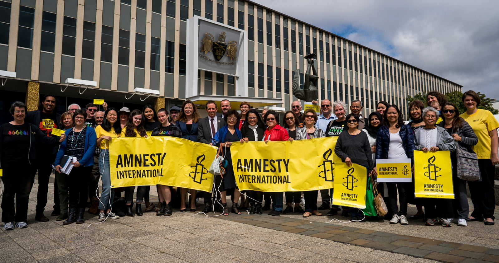 a group of people holding yellow Amnesty banners standing outside Parliament House in Canberra