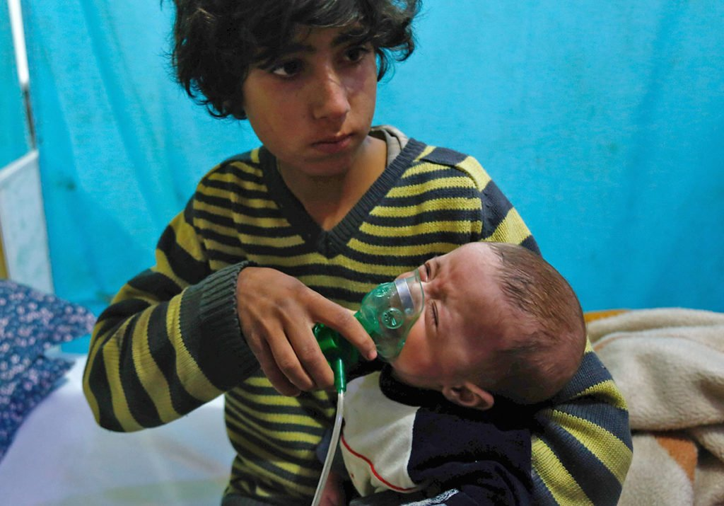 A Syrian boy holds an oxygen mask over the face of an infant at a make-shift hospital following a reported gas attack in Eastern Ghouta.